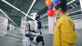 Smiling lady is giving colourful balloons to a robot stock video footage