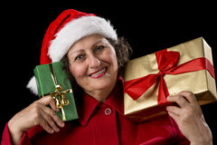Smiling Lady with Golden and Green Christmas Gifts. Smiling senior lady with a Father Christmas hat and red coat. She is holding a wrapped Christmas present in Royalty Free Stock Images