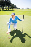 Smiling lady golfer kneeling on the putting green Stock Photo