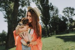 Smiling lady in hat is hugging her dog stock photos