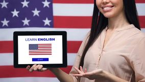 Smiling lady holding tablet with learn English language app, USA flag background. Stock footage stock video footage
