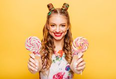 Smiling lady holding two huge colorful lollypops royalty free stock image