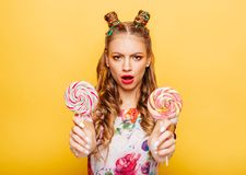 Smiling lady holding two huge colorful lollypops. Young smiling lady holding two huge colorful lollypops. Amasing young woman fills happy and holding big candies Royalty Free Stock Photos