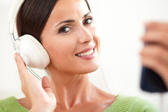 Smiling lady listening to music on headphones Royalty Free Stock Images