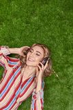 Smiling lady listening to music on lawn stock photography