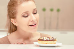 Smiling lady looks at donut with an intention to Stock Photography