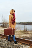 Smiling Lady with old suitcase walking along the railroad Royalty Free Stock Photography