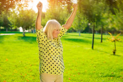 Smiling lady with raised arms. Royalty Free Stock Image