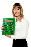 Smiling lady showing big green calculator. Cheerful businesswoman holding big calculator Royalty Free Stock Photography