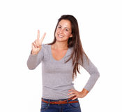 Smiling lady showing victory sign with her fingers Royalty Free Stock Photos
