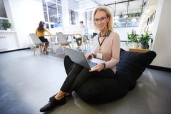 Smiling lady sitting in bean bag. Smiling mature lady in glasses wearing conference badge on neck sitting in bean bag and using modern laptop while looking at stock image