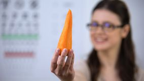 Smiling lady in spectacles proposing fresh carrot, organic nutrition for vision. Stock footage stock footage