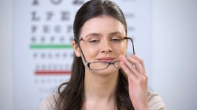 Smiling lady taking off glasses and showing case with contact lens, improvement. Stock footage stock footage