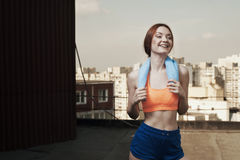 Smiling lady with towel around neck after workout Stock Image