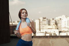 Smiling lady with towel around neck after workout Royalty Free Stock Photos