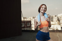 Smiling lady with towel around neck after workout Royalty Free Stock Images