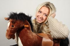 Smiling lady with toy horse Royalty Free Stock Images