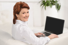 Smiling lady using a laptop while sitting on sofa Royalty Free Stock Image