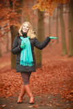 Smiling lady walking through park. Outdoor nature leisure foliage vegetation concept. Smiling lady walking through park. Young blonde taking a walk in autumnal Stock Image