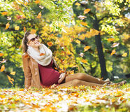 Smiling lady watching flying leaves Royalty Free Stock Photography