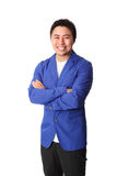 Smiling laid back businessman in blue blazer. Young good looking man standing wearing a blue jacket. White background Stock Photo