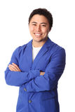 Smiling laid back businessman in blue blazer. Young good looking man standing wearing a blue jacket. White background Stock Photos