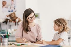 Smiling language tutor working with a little boy, drawing with c stock photography