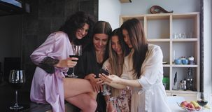 Smiling large charismatic ladies in stylish pajamas preparing for a bachelorette party drinking some wine and looking