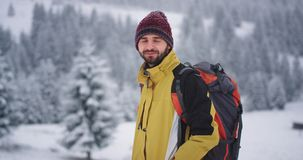Smiling large happy tourist man in front of the camera he traveling in the mountain, in the winter amazing landscape. Around snowy forest. 4k stock video