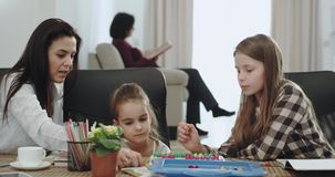 Smiling large mature mother with her two daughters playing together on table games spending a family time together stock video