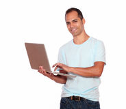 Smiling latin adult man using his laptop computer. Portrait of a smiling latin adult man looking at you while is using his laptop computer on isolated background Royalty Free Stock Photo