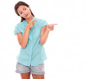 Smiling latin girl pointing to her left Royalty Free Stock Photos