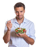 Smiling latin man eating salad Royalty Free Stock Image