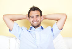 Smiling latin man on white couch Royalty Free Stock Photo