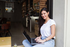 Smiling latin woman posing for the camera while keyboarding on her laptop computer during lunch break in sidewalk cafe. Female student connecting to wireless via Stock Photo