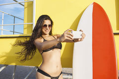 Smiling Latin women in bikini photographing herself with smart phone camera while standing with surfboard near lifeguard house Royalty Free Stock Photo