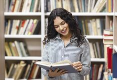 Free Smiling Latina Woman Reading A Book At Library Stock Image - 170451961