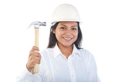 Smiling latino girl with hammer. And hard hat isolated on white Royalty Free Stock Images