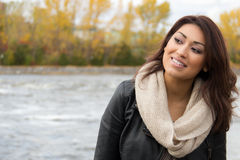 Smiling Latino woman posing outdoors during autumn Stock Photo