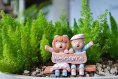 Smiling and laughing boy and girl clay doll with welcome word Stock Photo