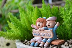 Smiling and laughing boy and girl clay doll with welcome word. In the garden, Happiness concept Royalty Free Stock Photography