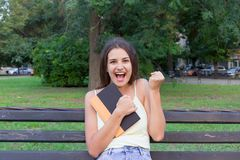 Smiling and laughing brunette woman is hugging book and showing yes gesrure in park. I got it. I did it.  stock photo