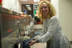 Smiling Laundromat girl inserting clothes Stock Photo