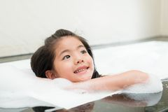 Smiling leisurely female kid relaxing on bathtub Stock Images