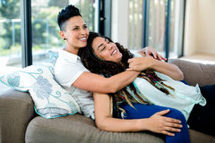 Smiling lesbian couple embracing and relaxing on sofa Royalty Free Stock Photos