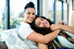 Smiling lesbian couple embracing and relaxing on sofa Royalty Free Stock Image