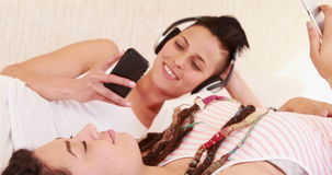 Smiling lesbian couple listening music together stock video
