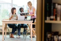 Smiling Librarian Assisting Students In Library Stock Image