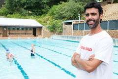 Smiling lifeguard standing with arms crossed Stock Photography