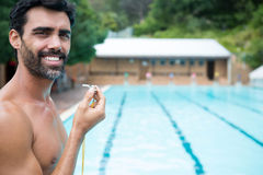 Smiling lifeguard standing with whistle near poolside Stock Images